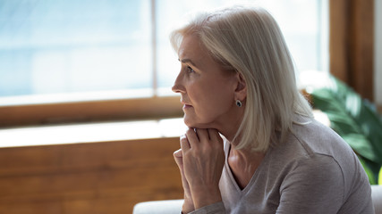 Profile unhappy upset older woman sitting alone and thinking about problems, feeling lonely, suffering from depression, dementia or mental disorder, frustrated mature female looking in distance