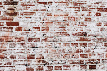 photo of an old brick wall covered with white paint