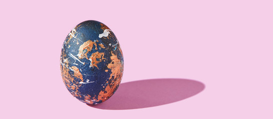 One decorative egg with hard shadow. Art easter concept. Single decorated like earth globe. Blue and gold object. Pink background. Horizontal