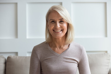 Head shot portrait smiling beautiful older woman looking at camera, making video call to...