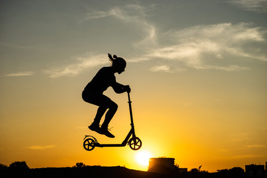 silhouette of a man riding and jumping on kick scooter with beautiful sunrise on background