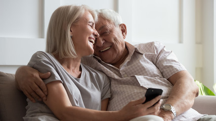 Happy older wife and husband cuddling close up, using phone together, laughing at funny video in...