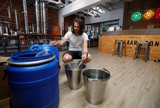Distiller Andre Pienaar mixes up a batch of 70 percent alcohol, a by-product of the gin making process, which he makes available as hand sanitiser to restrict the outbreak of coronavirus disease (COVID-19) spread in Cape Town