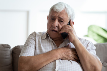 Upset older man touching chest, calling emergency, talking on phone, unhappy mature male having...