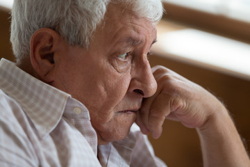 Head shot close up unhappy thoughtful melancholy older man lost in thoughts or memories, touching...