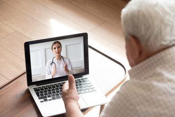 Close up older man talking with doctor by video call, using medical apps on laptop, service,...