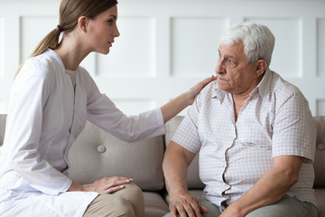 Caring doctor consulting, comforting older patient, touching shoulder, giving psychological help, sitting on couch together, serious mature man listening to woman caregiver wearing white uniform