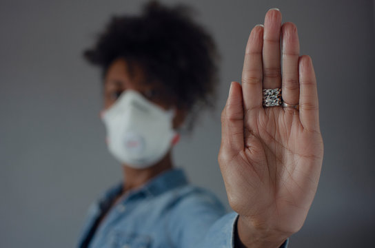 Black woman wearing a FFP3 mask and showing the palm of her hand as a stop gesture. Stop the spread of coronavirus.