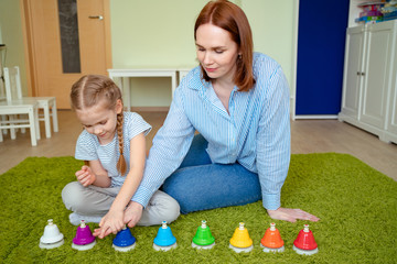 mom and daughter playing colourful musical bells