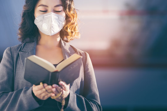 Asian girl chanting blessings of God and the Bible, hoping to give everyone a safe and healthy. She wore Hygienic masks to protect themselves from the spread of the virus and prevent air pollution.