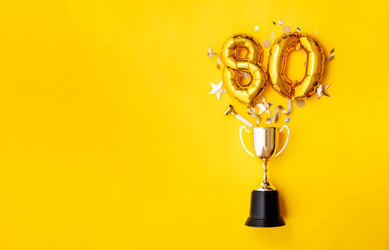 Number 80 gold anniversary celebration balloon exploding from a winning trophy
