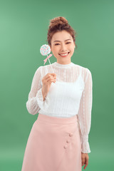 shot of beautiful young Asian woman. Pretty girl holding round candy and cheerfully smiling. Isolated green background
