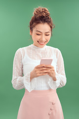 Portrait of happy young Asian woman holding smartphone over green background.