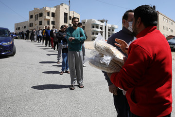 People stand in line to buy bread from a bus delivering food in front of their homes after Jordan announced it would extend a curfew indefinitely, amid concerns over the spread of coronavirus disease (COVID-19), in Amman