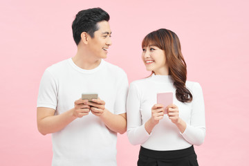 Image of asian man and woman using smartphones isolated over colorful background