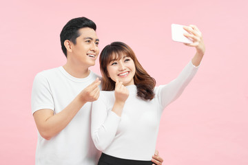Capture happy moments together. Happy young loving couple making selfie and smiling while standing against grey background