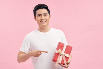 Handsome young man smiling and giving a red gift box to you isolated on pink background