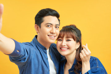 Self portrait of funny foolish cheerful adorable young cute couple smiling showing teeth, looking straight with opened mouths over yellow background, isolated