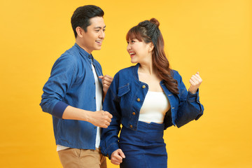 Affectionate interracial couple holding hands and dancing together over yellow background, having fun.