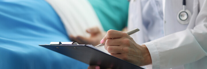 Focus on female tender hand holding pen and writing something in important documents. Beautiful doctor visiting ill patient. Healthcare and medicine concept