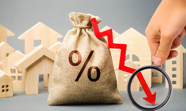 Money bag with percents, down arrow and miniature houses. The concept of low interest rates on mortgage loans or rentals. The percentage of real estate sales. Tax interest. Loan secured. Drop and fall