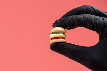 Colorful candy hamburger with a hand in black glove. Minimal food concept.