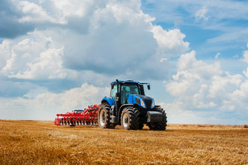 blue tractor in the field, agricultural machinery work, field and beautiful sky