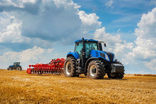 blue new tractor with red harrow in the field against a cloudy sky, agricultural machinery work
