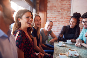 Group Of Male And Female Friends Meeting For Coffee Sitting At Table Together Wall mural