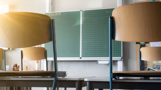 CORONAVIRUS - School closed - Empty classroom with high chairs and empty green blackboard / chalkboard