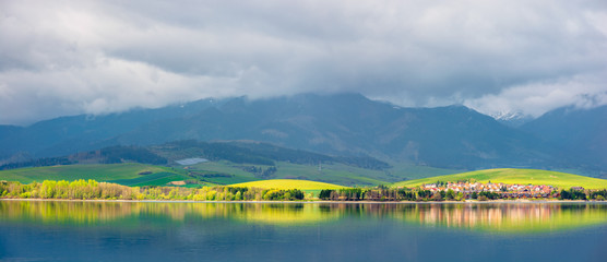 lake in mountains. cloudy day in springtime. rural fields on rolling hills. beautiful scenery of high tatra mountains in dappled light. gorgeous landscape of liptovska mara, slovakia