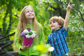 Two children planting vegetable in garden. American farm life. Eco resort activities. Summer leisure. Happy kid on summer field. Cute little farmers - sister and brother working with spud on field.