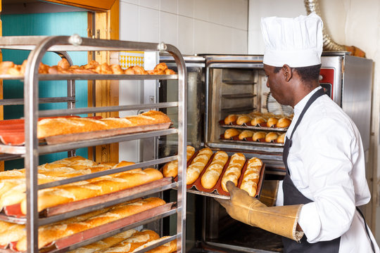 Worker of bakery putting baked baguettes on tray rack