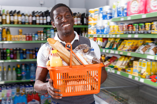 Smiling African man with shopping cart