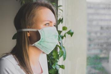 Woman in medical mask near window. Quarantine at home. Wall mural