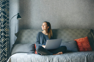 Girl working on laptop from home or student studying from home or freelancer. Or she is watching a video or using the Internet Wall mural