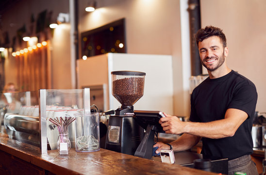 Portrait Of Male Coffee Shop Owner Standing At Sales Desk