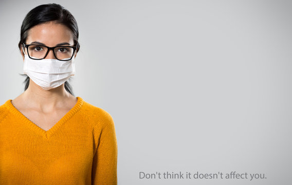 Сoronavirus. Serious hispanic young woman in medical mask on a gray background with space for text.