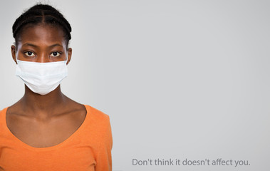 Сoronavirus. Serious african woman in medical mask on a gray background with space for text.