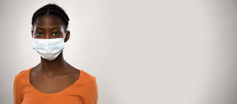 Сoronavirus. Serious africanamerican woman in medical mask on a gray background.