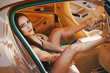 Young brunette lady in sexy lingerie sitting on a backseat of a luxury car. Glamour woman in gold car. Sensual brunette woman in sexy underwear in car salon back seat.