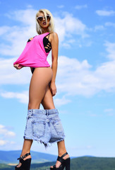 Vogue fashion style portrait of young girl with trousers down. Female model denim pants down.