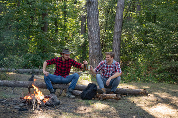 Man doing mans job. Two young guy sitting in the forest and drinking beer near campfire. Young people having a camping. Resting after hard work. Two handsome men friends on camping near campfire.