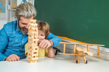 Father and son playing jenga game at home. Homework help. Individual teaching. Private kids tutoring. Learning concept. Preschool tutorship