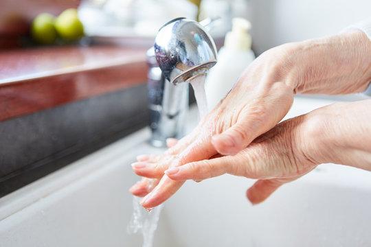 Alte Frau beim Hände waschen mit Seife