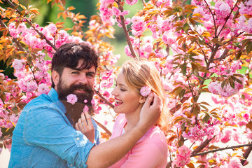 Lovers on a walk in a spring blooming park. Young happy couple in love outdoors. Spring portrait of beautiful happy couple. Romantic date couple concept.
