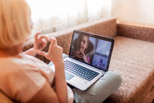 Cute girl talking with her grandmother within video chat on laptop, life in quarantine time