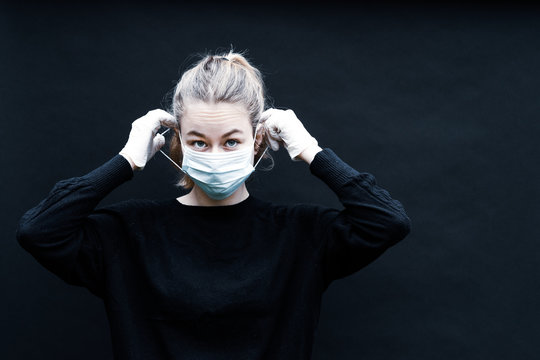 une jeune femme blonde se place un masque de protection sur le visage