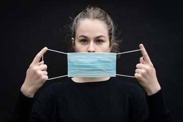 une jeune fille sur le point de mettre un masque de protection