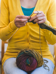 Young woman is knitting.